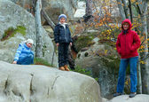 Lofty stones in autumn forest and family — Stock Photo