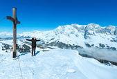 Turismo cerca de la cruz en la cima de la montaña de invierno — Foto de Stock