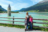 The bell tower in Reschensee and family (Italy). — Stock Photo