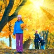 Family in autumn sunshiny maple park — Stock Photo #36295559