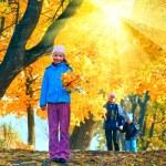 Family in autumn sunshiny maple park — Stock Photo #36295559