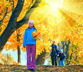 Family in autumn sunshiny maple park — Stock Photo