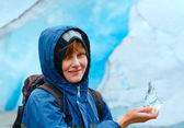 Woman with ice piece near Nigardsbreen glacier (Norway) — Stock Photo