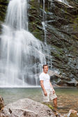Young man and waterfall — Stock Photo