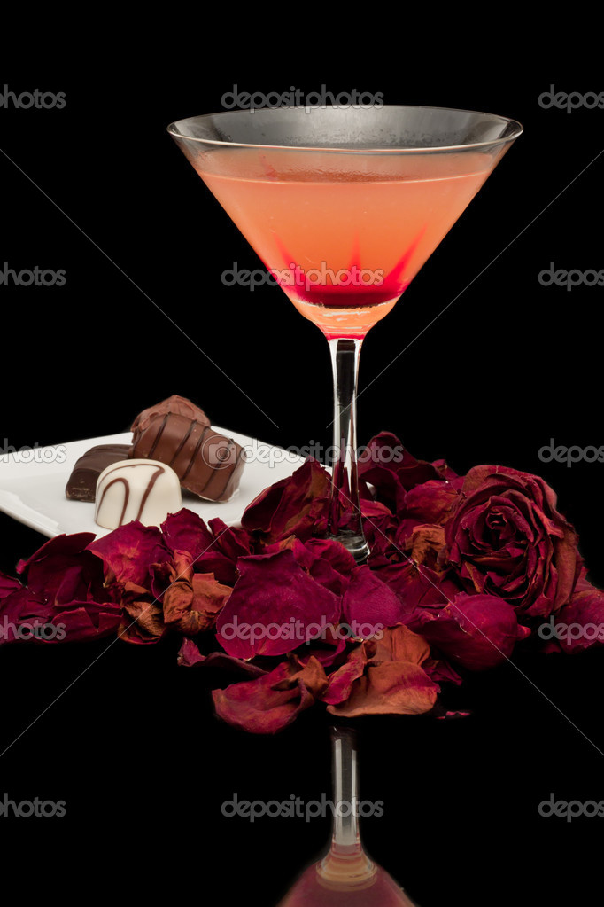 Pink and red cocktail isolated on a black background with dried rose petals around the base of the glass — Stock Photo #13183343