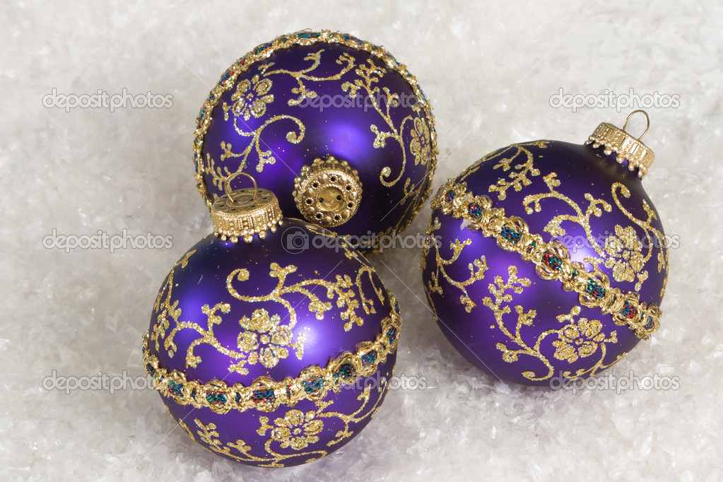 Purple christmas ornaments arranged in white snow as a background — Stock Photo #17054703