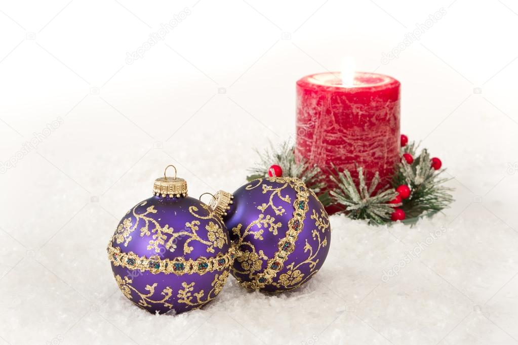 Purple christmas ornaments in snow with a red holiday candle behind them  Stock Photo #17054769