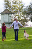 Mom And daughter walking the dog — Stock Photo