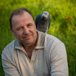 Постер, плакат: Man with parrot sitting on the shoulder