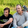 The teenager and his dad with a gray parrot Jaco. — Stock Photo