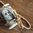Hundred dollar bills rolled up with rope on wooden table : copyspace — Stock Photo #39738923