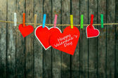 Cute big red heart hanging on the clothesline. On old wood background. — Stock Photo