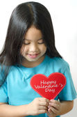 Color photo of a 7 year old, asien black haired girl holding an heart-shaped — Stock Photo