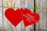 Cute big red heart hanging on the clothesline. On old wood background. — Stockfoto