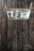 One Hundred Dollars hanging on the clothesline.old wood background. — Stock Photo