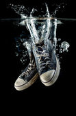 Splashing  old dirty sneakers on a black  background — Stock Photo
