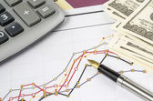 Fountain pen and calculator on the financial graph — Stok fotoğraf