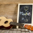 """Ukulele guitar and blackboard with the word """"Music"""" written on wooden background — Stock Photo #49035553"""