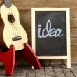 """Ukulele guitar and blackboard with the word """"idea"""" written on wooden background — Stock Photo #49035569"""