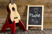 """Ukulele guitar and blackboard  with the word  """"Music""""  written on wooden background — Stock Photo"""
