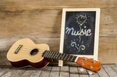 "Ukulele guitar and blackboard  with the word  ""Music""  written on wooden background — Stock Photo"