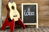 """Ukulele guitar and blackboard  with the word  """"idea""""  written on wooden background — Stock Photo"""