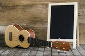 Ukulele guitar and  blank blackboard  on wooden background — Stock Photo