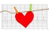 Red paper heart hanging on the clothesline on  electrocardiogram — Stock Photo