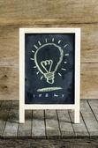 Light Blub Chalkboard Drawing on wooden background — Stockfoto