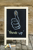 Thumb up  Chalkboard Drawing  on wooden background — Stockfoto