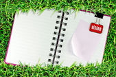Blank page of note book on grass and Binder Clip — ストック写真