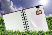 Blank notebook on the Green Meadow and Blue Sky Background — Stock Photo