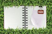 Page blanche du carnet de notes sur l'herbe et liant clip — Photo