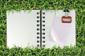 Blank page of note book on grass and Binder Clip — Stock Photo