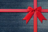 Blue Jeans background with Red Bow — Stock Photo