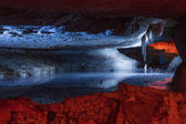 Underground lake reflects ceiling cave formations. — Stock Photo