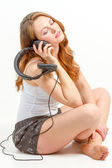 Seated girl contemplates about audio — Stock Photo