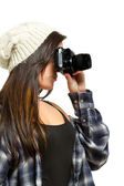 Young woman with brown hair holds camera — Stock Photo