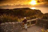 身份不明的女孩看美丽风景的海和煎饼岩在日落时间,煎饼岩石,南岛,新西兰 — 图库照片
