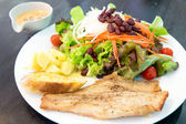 Fish steak with salad, dipping sauce and garlic bread — Stock Photo