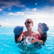 Happy family splashing in swimming pool on a tropical resort — Stock Photo #13736847