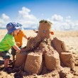 Two boys building large sandcastle on the beach — 图库照片
