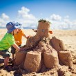 Two boys building large sandcastle on the beach — ストック写真