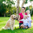 Mother and her two sons in the park with a golden retriever — Stock Photo