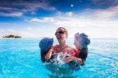 Familia feliz chapoteando en la piscina en un complejo hotelero tropical — Foto de Stock