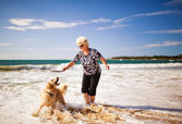 Woman playing on the beach with golden retriever — Stock Photo
