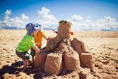 Dois rapazes edifício grande castelo de areia na praia — Foto Stock