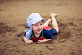 Little smiling boy in the mud puddle — Stock Photo