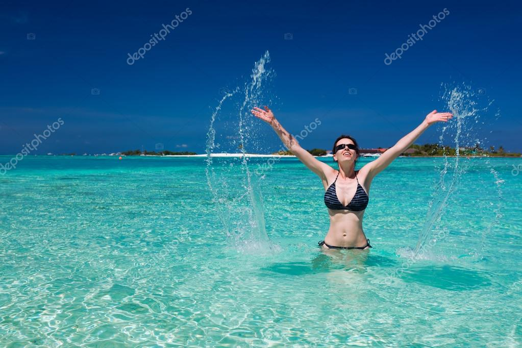 Beautiful woman jumps out of the sea leaving a big splash — Stock Photo #13736846