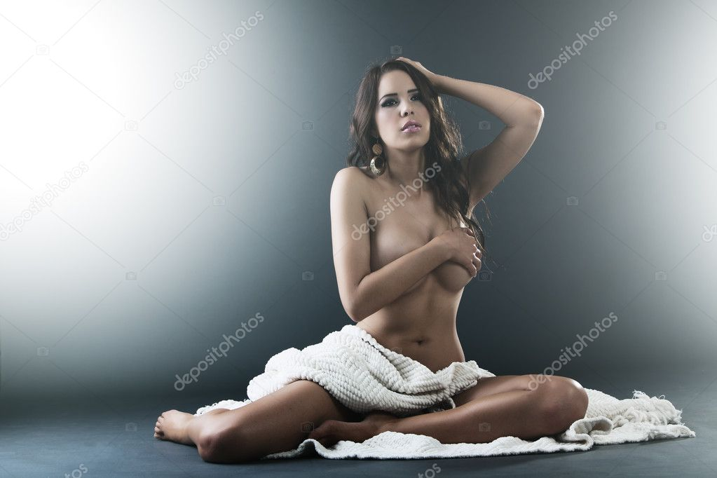 Beautiful Sensual nude woman sits covered by white cloth and hands — Stock Photo #13736869